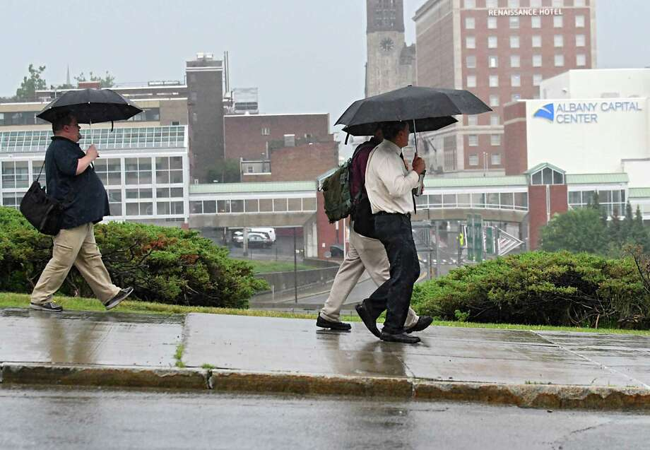 People use umbrellas as they walk along Madison Ave. on a rainy afternoon Wednesday, July 12, 2017 in Albany, N.Y. (Lori Van Buren / Times Union) Photo: Lori Van Buren, Albany Times Union