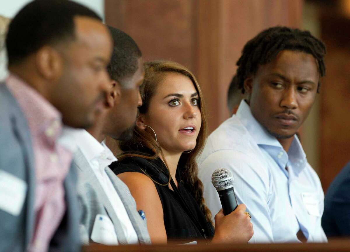 Kassidy Cook, Olympic diver and 2013 graduate of The Woodlands High School, speaks as Brandon Marshall, NFL wide receiver with the New York Giants, looks on during a sports forum titled