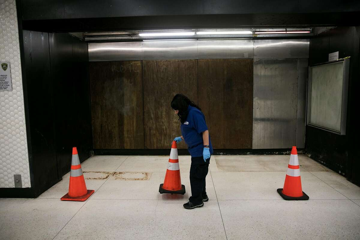 The BART custodian, Lucy Villanueva, puts cones around a closed off area of Powell Street BART station in San Francisco. Thursday, July 13, 2017.