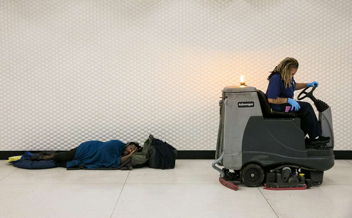 The BART custodian, Heather Oliver, cleans the floors around a homeless man at the Powell Street BART station in San Francisco, Calif. Thursday, July 13, 2017.