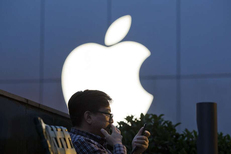 FILE - In this Friday, May 13, 2016, file photo, a man uses his mobile phone near an Apple store in Beijing. On Wednesday, July 12, 2017, Apple announced it will open a data center in mainland China with ties to the country's government, raising concerns about the security of iCloud accounts that store personal information transferred from iPhones, iPads and Mac computers there. (AP Photo/Ng Han Guan, File) Photo: Ng Han Guan, Associated Press