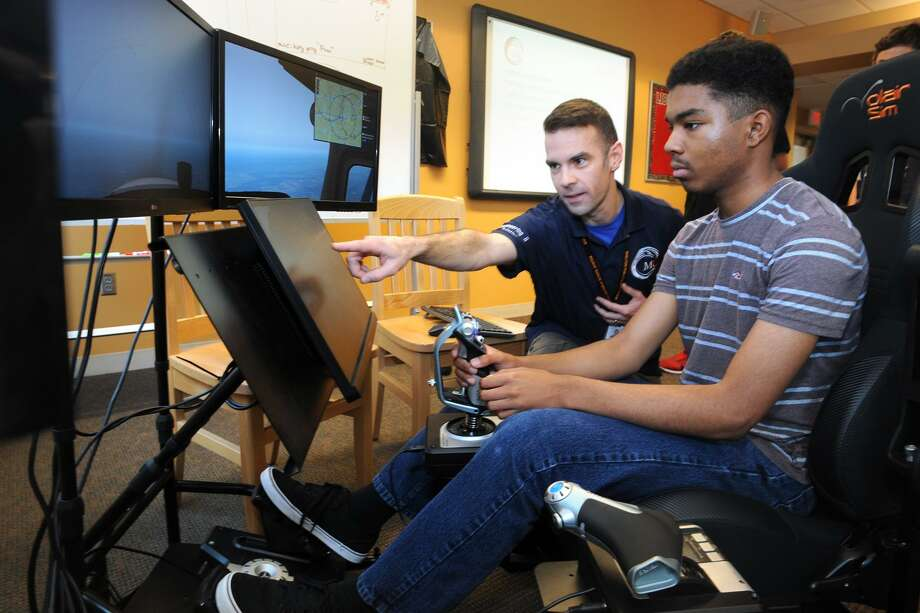 Instructor Gemo Yesil helps student Narmer Bazile as he flies a flight simulator during an Engineering & Aviation Summer Camp at the Perry School, in Shelton, Conn. July 13, 2017. Photo: Ned Gerard / Hearst Connecticut Media / Connecticut Post