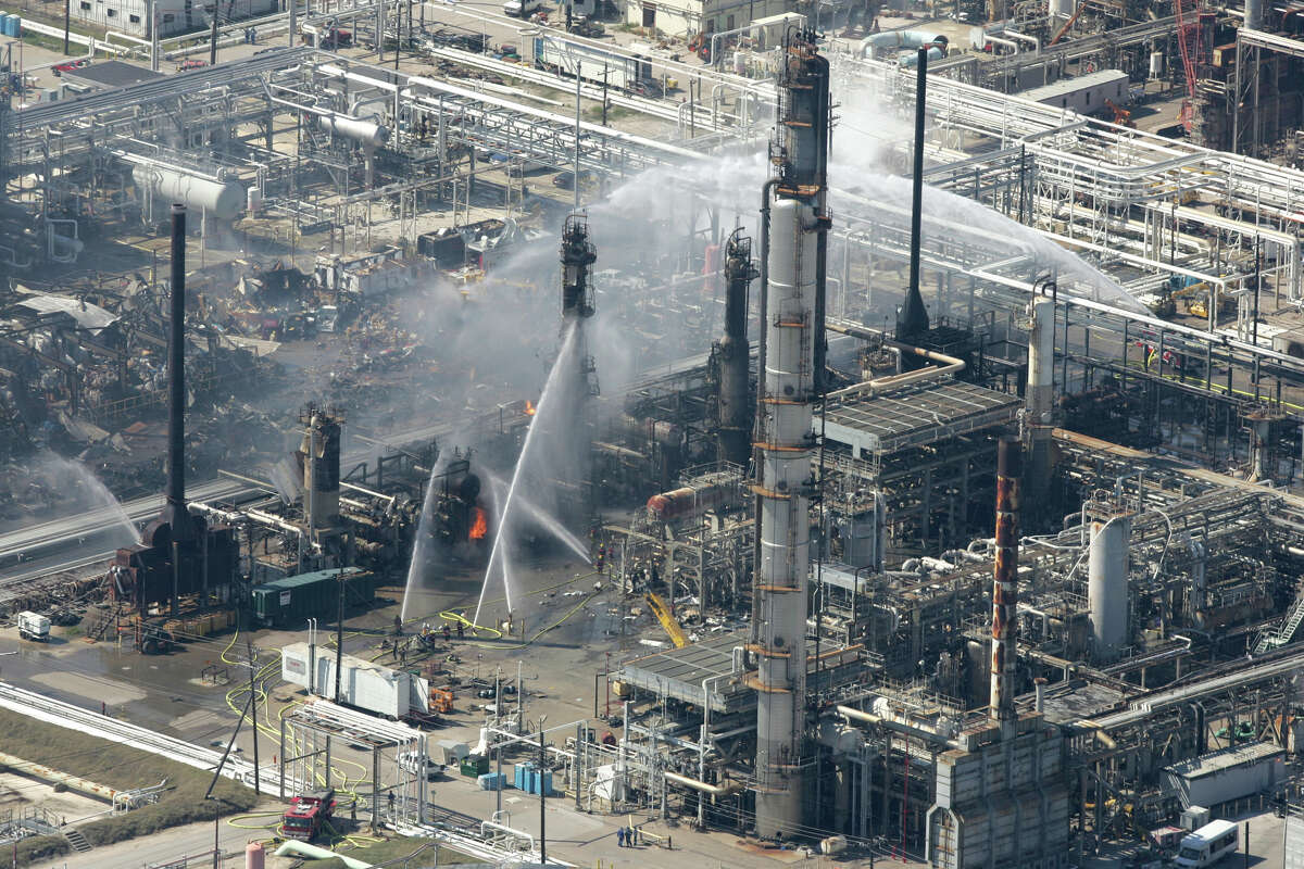 Firefighters pour water on a smoldering unit following an explosion that killed 15 people and injured more than 170 at the BP refinery in this March 23, 2005, file photo in Texas City. (Brett Coomer / Houston Chronicle)