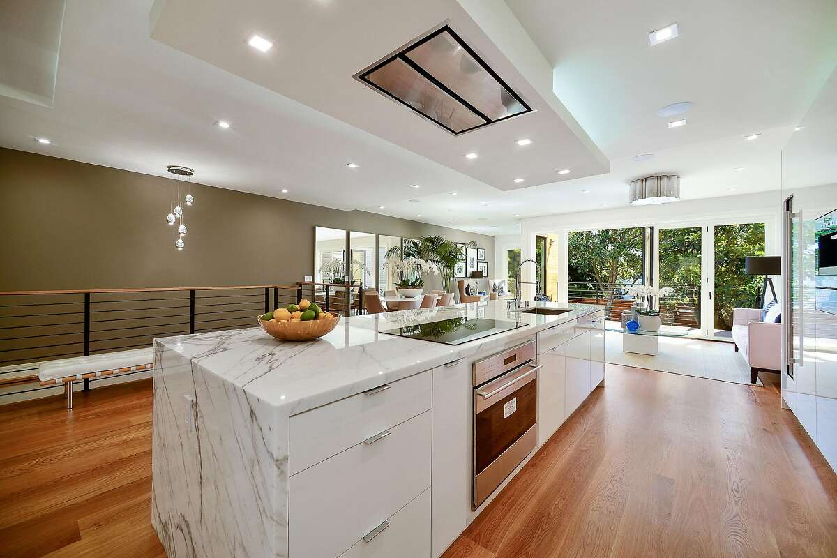 The contemporary kitchen features integrated appliances like an induction cooktop.�