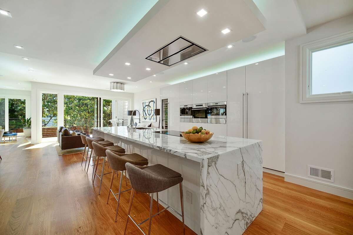 The great room revolves around a gleaming contemporary kitchen featuring a marble island with waterfall edges.�