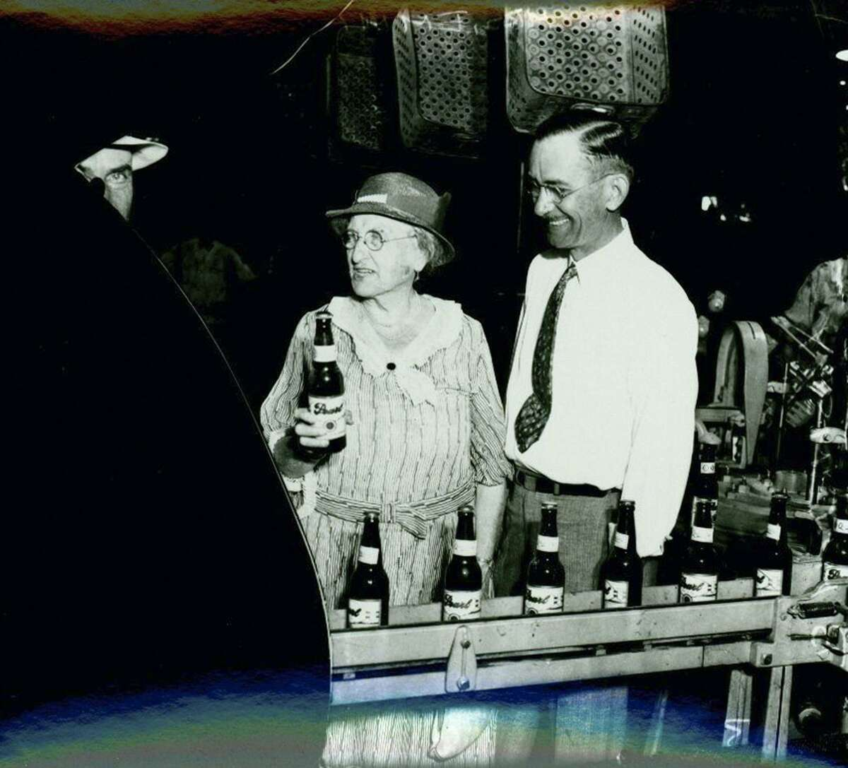Emma Koehler, left, holding the first bottle of beer produced by Pearl Brewery after the repeal of Prohibition in 1933. Beside her is general manager B.B. McGimsey.