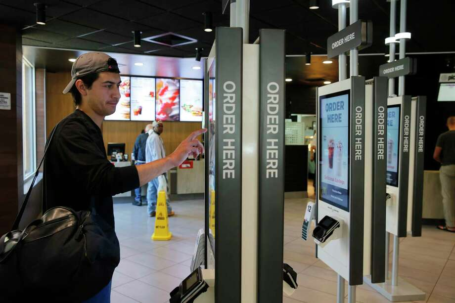 In this Thursday, June 1, 2017, photo, Brandon Alba from Milwaukee, orders food at a self-service kiosk at a McDonald's restaurant in Chicago. The company that helped define fast food is making supersized efforts to reverse its fading popularity and catch up to a landscape that has evolved around it. That includes expanding delivery, digital ordering kiosks in restaurants, and rolling out an app that saves precious seconds. (AP Photo/Charles Rex Arbogast) ORG XMIT: ILCA401 Photo: Charles Rex Arbogast / Copyright 2017 The Associated Press. All rights reserved.