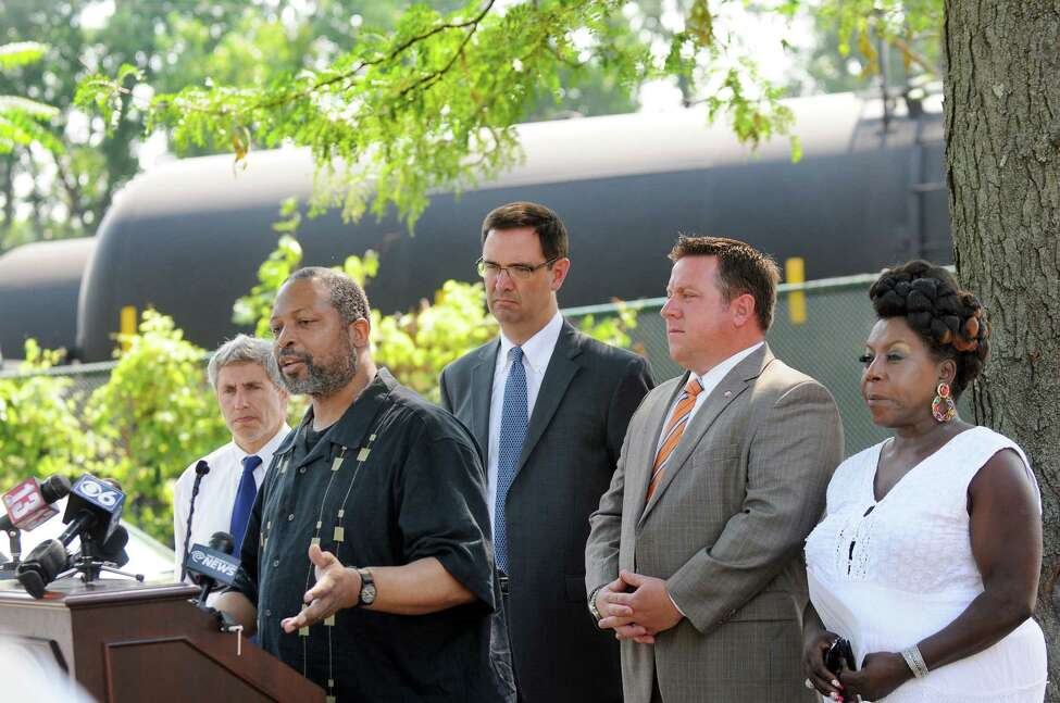 Albany County Legislator Merton Simpson, second from left, talks about the oil trains parked behind the apartments on Wednesday, July 23, 2014, at Ezra Prentice Homes in Albany, N.Y. Joining him, from left, are county attorney Tom Marcelle, executive director Peter Iwanowicz of Environmental Advocates, Albany County Executive Dan McCoy and county legislator Norma Chapman. (Cindy Schultz / Times Union)