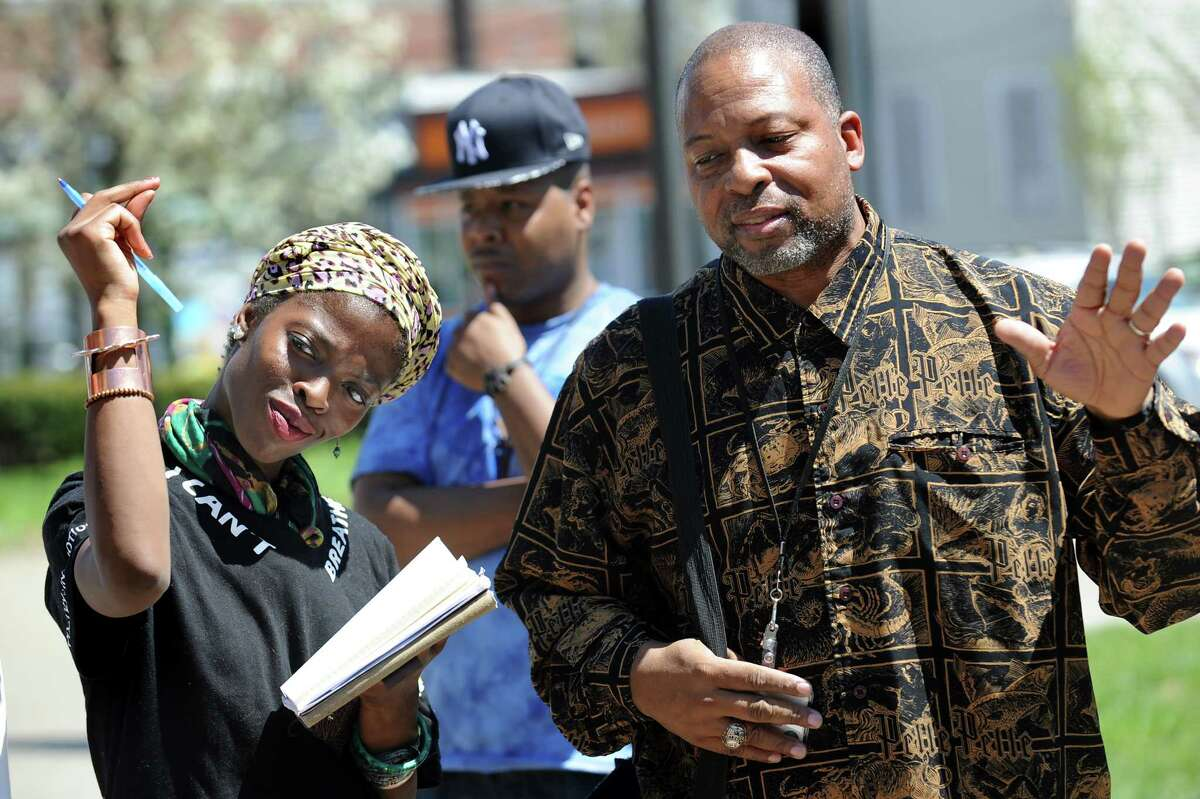 Amani Olugbala of Capital Area Against Mass Incarceration, left, snaps in support of points made by Albany County Legislator Merton Simpson, right, during a rally for social justice on Saturday, May 2, 2015, at the Albany Police Headquarters in Albany, N.Y. (Cindy Schultz / Times Union)