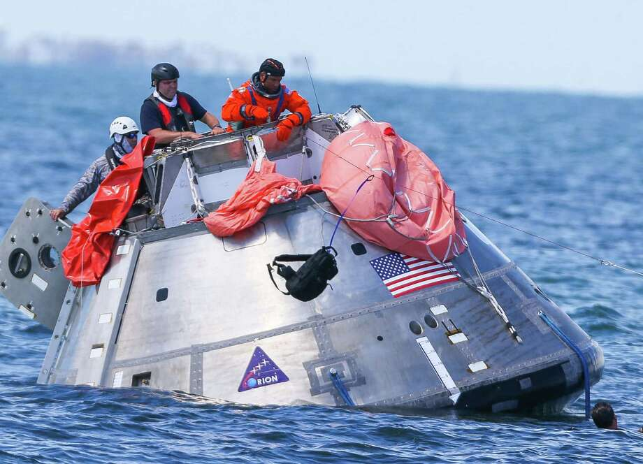 NASA astronaut Victor Glover throws a survival pack attached to a line attached to a life raft into the water while practicing an emergency egress situation aboard the Orion capsule they are using for recovery testing about four miles off of Galveston Island in the Gulf of Mexico, Thursday, July 13, 2017. The testing is the first time since the Apollo program that NASA has practiced such egress techniques from a capsule in open water. (Mark Mulligan / Houston Chronicle) Photo: Mark Mulligan / Houston Chronicle / Mark Mulligan / Houston Chronicle
