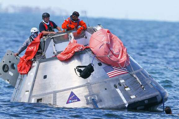 NASA astronaut Victor Glover throws a survival pack attached to a line attached to a life raft into the water while practicing an emergency egress situation aboard the Orion capsule they are using for recovery testing about four miles off of Galveston Island in the Gulf of Mexico, Thursday, July 13, 2017. The testing is the first time since the Apollo program that NASA has practiced such egress techniques from a capsule in open water. (Mark Mulligan / Houston Chronicle)