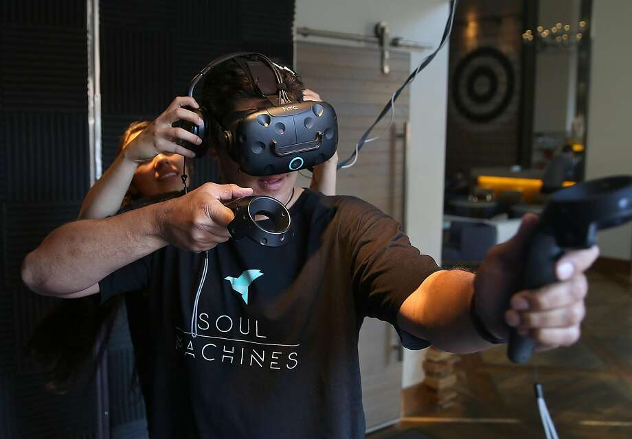 VR guide Angelica Solloa (rear) sets up gamer Shaun Paga for an archery game with an HTC Vive VR at the ExitVR cube at Hotel Zetta in San Francisco. Photo: Liz Hafalia, The Chronicle