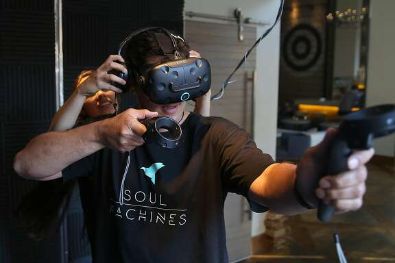 Exit Reality VR guide Angelica Solloa (behind) sets gamer Shaun Paga (front) for an archery game with an HTC Vive VR at the ExitVR cube at Hotel Zetta on Tuesday, July 11, 2017 in San Francisco, Calif.