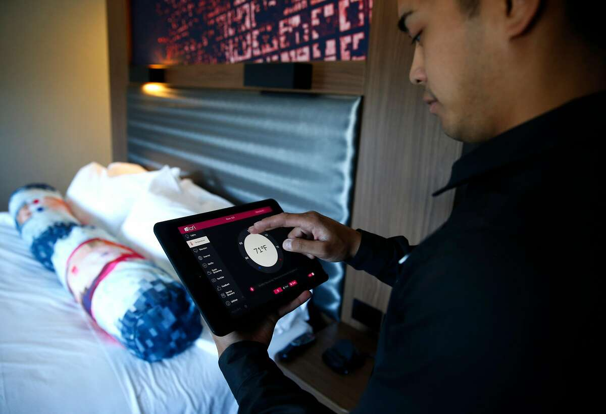 Front desk employee Chris Resurreccion demonstrates controls in a room at the Aloft Santa Clara hotel in San Jose.