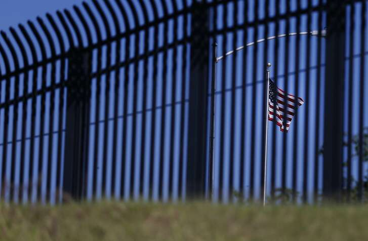 The United States flag waves in the wind as seen through the border fencing in Eagle Pass, Texas on Wednesday, Oct. 5, 2016. (Kin Man Hui/San Antonio Express-News)