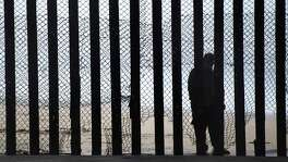 A pair of immigration bills passed by the U.S. House demonstrates how little lawmakers understand about immigration. Here, a man stands on the Mexico side of a border fence separating the beaches at Border Field State Park, in San Diego, California.