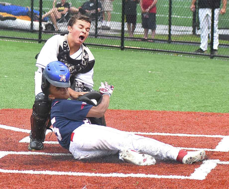 Norwalk's Vance Ward, bottom, is tagged out at the plate by Trumbull catcher Justin Delaney during Thursday's Babe Ruth Baseball 13-year-old tournament championship round game at Brien McMahon High School in Norwalk. Photo: John Nash / Hearst Connecticut Media / Norwalk Hour