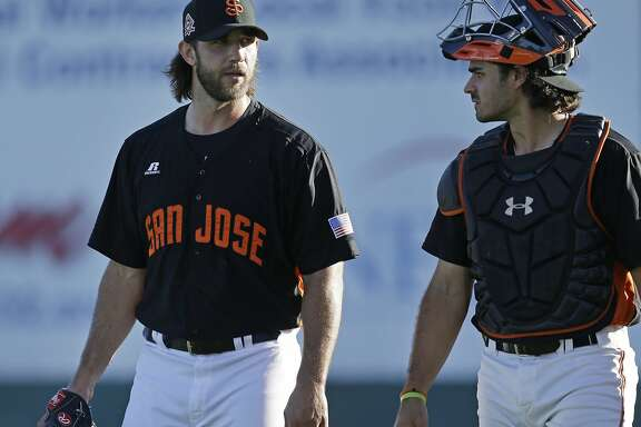 San Francisco Giants pitcher Madison Bumgarner, left, speaks with catcher Aramis Garcia during a rehab assignment with the San Jose Giants as they host the Modesto Nuts in a baseball game Monday, July 10, 2017, in San Jose, Calif. Bumgarner has been on the disabled list since suffering a sprained AC joint in his pitching shoulder along with bruised ribs after a dirt bike accident earlier this season. (AP Photo/Ben Margot)