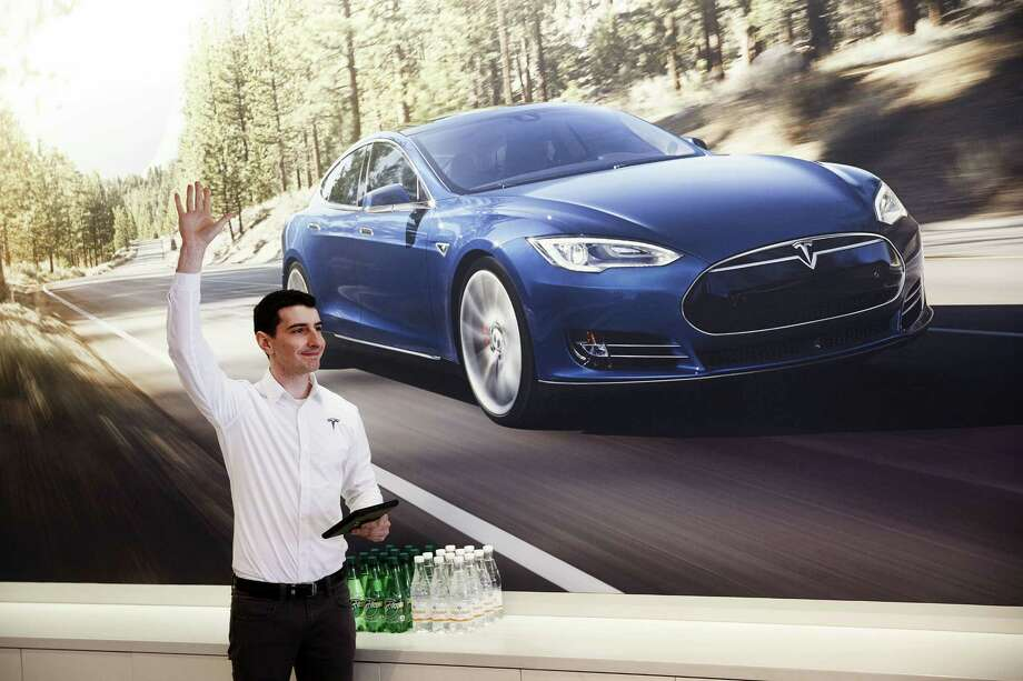 An employee signals he is ready to assist a customer with pre-ordering Tesla's Model 3 outside a store in Santa Monica, Calif., in March 2016. Photo: Patrick T. Fallon, Bloomberg / Bloomberg
