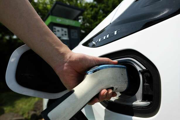 A man attaches a charging plug to a General Motors Co. (GM) Chevrolet 2017 Volt hybrid electric vehicle (EV) at a charging station in Jeju, South Korea, on Wednesday, June 14, 2017. The election of Moon Jae-in as South Korea's new president implies a shift in the nation's approach to energy, as he supports policies that favor natural gas and renewables at the expense of nuclear and coal, according to Bloomberg New Energy Finance. Photographer: SeongJoon Cho/Bloomberg