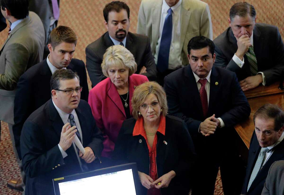 Lawmakers, including sponsor Texas Rep. Larry Phillips, R-Sherman, front left, get clarification on an amendment to a licensed open carry of handguns bill in the House Chamber at the Texas Capitol, Wednesday, May 27, 2015, in Austin, Texas. (AP Photo/Eric Gay)