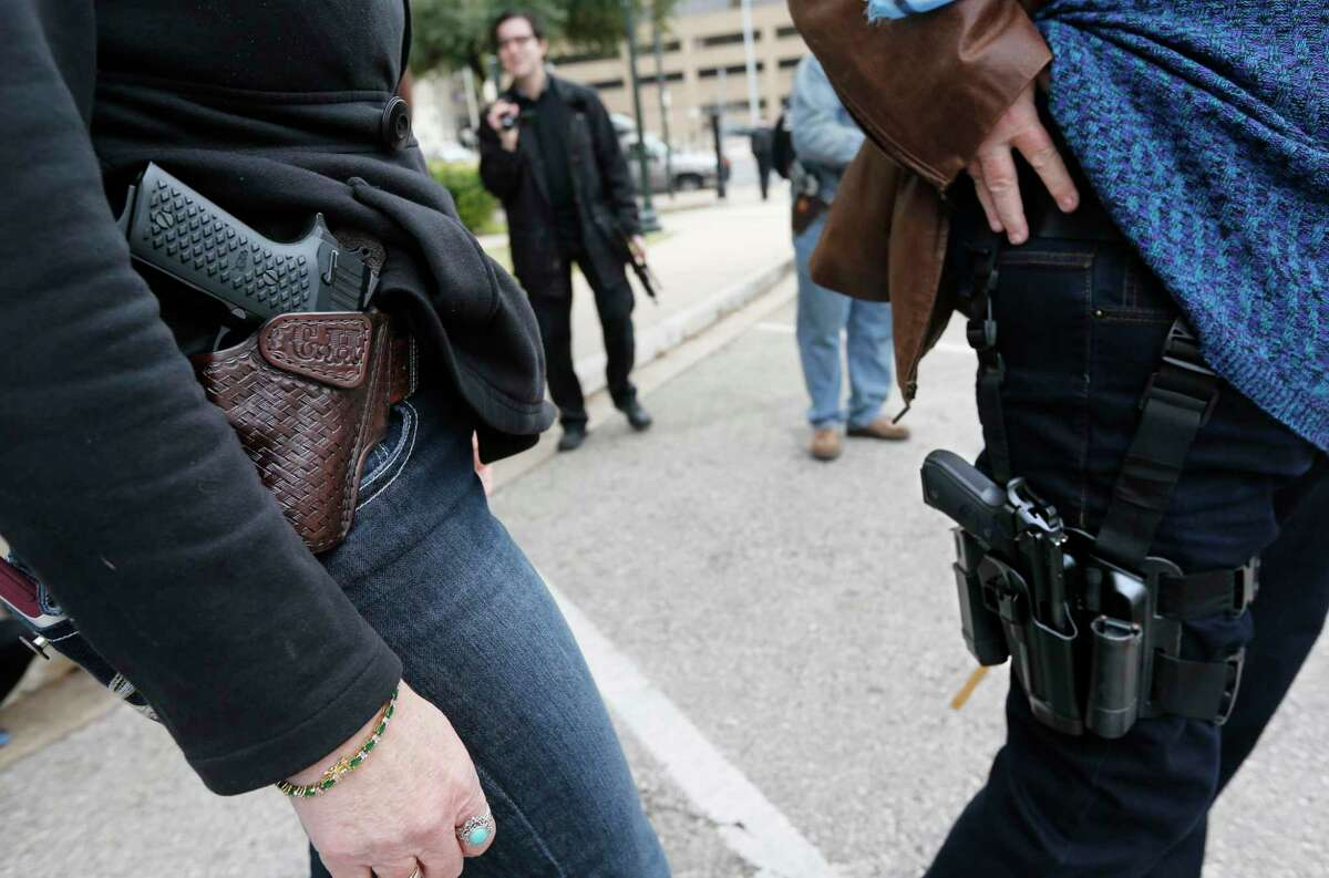AUSTIN, TX - JANUARY 1: Two women compare handgun holsters during an open carry rally at the Texas State Capitol in Austin, Texas. On January 1, 2016, the open carry law took effect in Texas, and 2nd Amendment activists held an open carry rally at the Texas state capitol on January 1, 2016 in Austin, Texas. (Photo by Erich Schlegel/Getty Images)