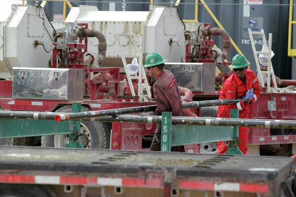 Halliburton employees move pipe at a three-wellhead hydraulic fracturing site last month in Midland.