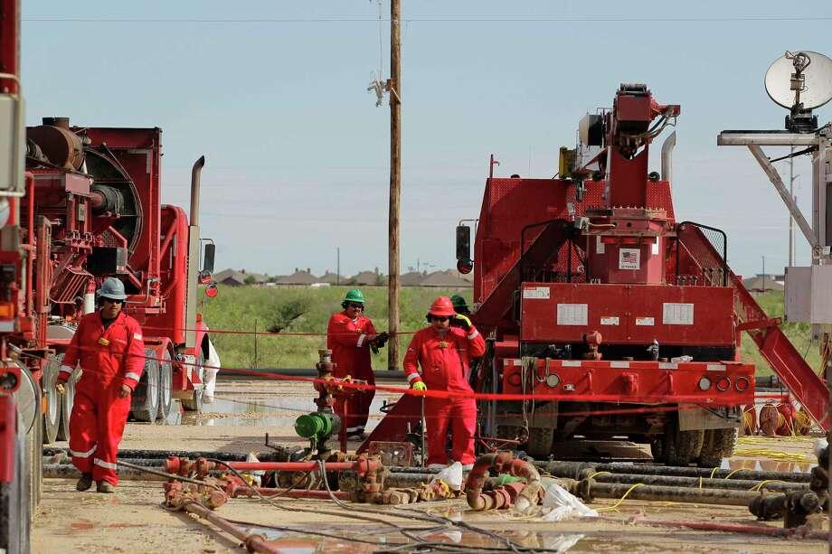 Halliburton's employees work at a three wellhead fracking site Monday, June 26, 2017, in Midland. ( Steve Gonzales  / Houston Chronicle ) Photo: Steve Gonzales, Staff / © 2017 Houston Chronicle