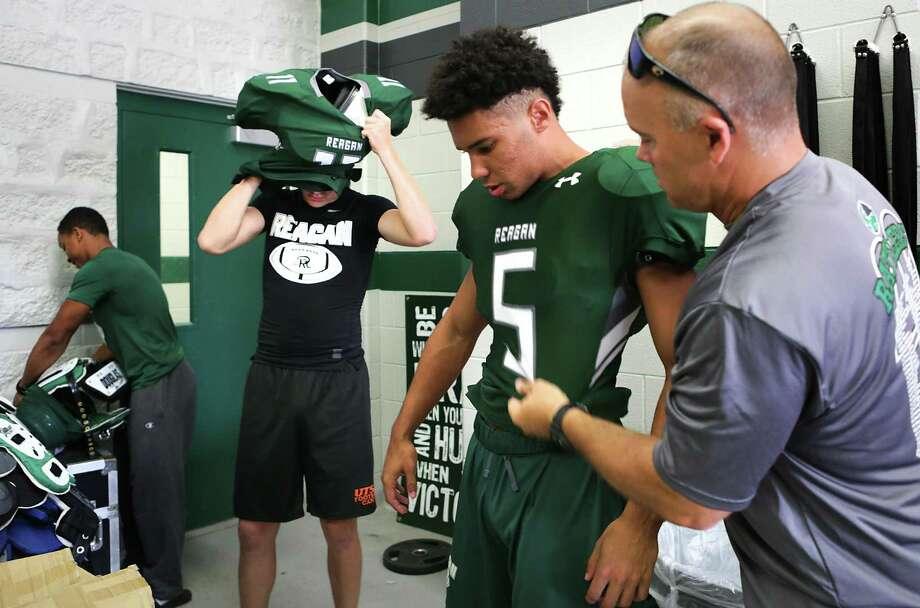 Reagan coach Lyndon Hamilton (right) helps Lucas Eatman (5) put on a new jersey before the start of fall practice in 2017. Photo: Bob Owen /San Antonio Express-News / ©2017 San Antonio Express-News