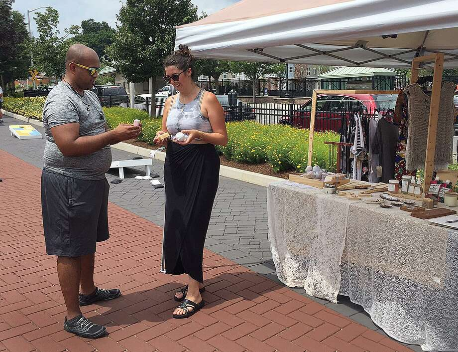 Meagan Cann of Workspace Collective shows handmade soaps to Joseph Purayidthil during the Downtown Chow-Down in Danbury, Conn., on Thursday, July 13, 2017. Photo: Chris Bosak / Hearst Connecticut Media / The News-Times
