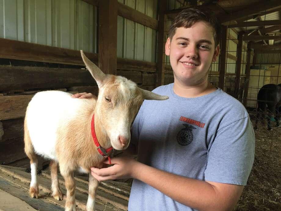 EHS student Trevor Huene with one of his goats on Arrow Mark Farm. Photo: Julia Biggs