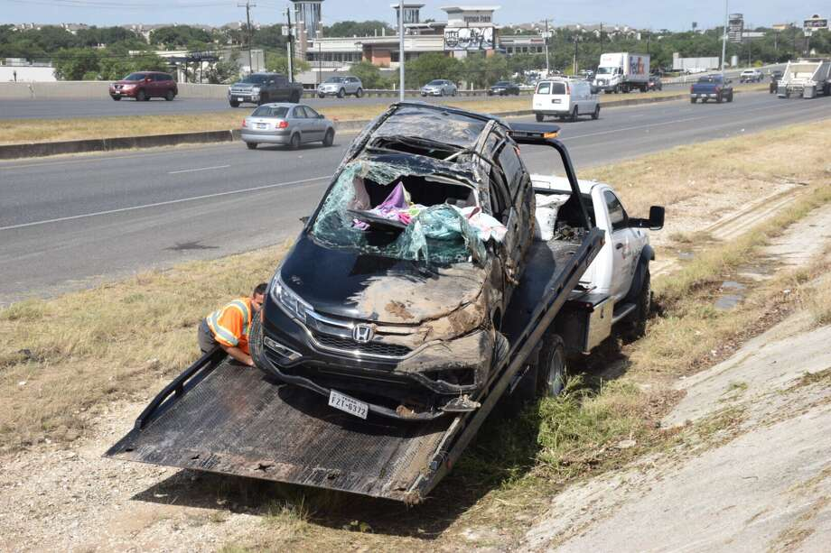 Three people were hospitalized Friday, July 14, 2017, after a rollover crash on the North Side. Photo: Caleb Downs / San Antonio Express-News