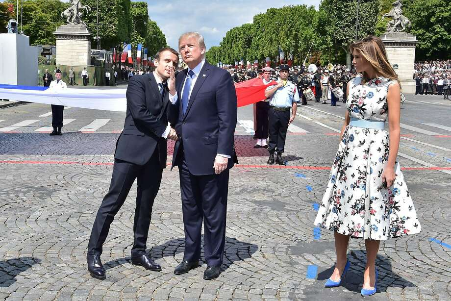 French President Emmanuel Macron shakes hands with President Trump, next to first lady Melania Trump, during the Bastille Day parade along the Champs-Elysees in Paris. Photo: CHRISTOPHE ARCHAMBAULT, AFP/Getty Images