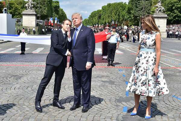 TOPSHOT - French President Emmanuel Macron (L) shakes hands with US President Donald Trump, next to US First Lady Melania Trump, during the annual Bastille Day military parade on the Champs-Elysees avenue in Paris on July 14, 2017. The parade on Paris's Champs-Elysees will commemorate the centenary of the US entering WWI and will feature horses, helicopters, planes and troops. / AFP PHOTO / POOL AND AFP PHOTO / CHRISTOPHE ARCHAMBAULTCHRISTOPHE ARCHAMBAULT/AFP/Getty Images