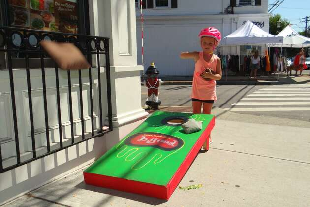 Shay Todd, 4, of Fairfield, plays cornhole outside b.good during Fairfield's Summer Sidewalk Sale & Street Fair last year. The annual event returns, rain or shine, to downtown Fairfield on Saturday, July 22.