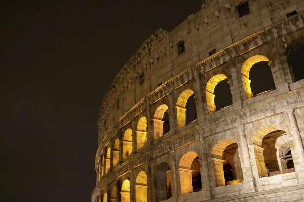 ROME, ITALY - JANUARY 02: The Colosseum also known as the The Flavian Amphitheatre illumintated at night on January 02, 2017 in Rome, Italy. The Colosseum or the Flavian Amphitheatre is an oval amphitheatre in the centre of the city of Rome. Built of concrete and sand, it is the largest amphitheatre ever built and was the largest amphitheater in the Roman Empire.The Colosseum is situated just east of the Roman Forum. Construction began under the emperor Vespasian in AD 72 and was completed in AD 80. These three emperors are known as the Flavian dynasty, and the amphitheatre was named in Latin for its association with their family name (Flavius). (Photo by Athanasios Gioumpasis/Getty Images).