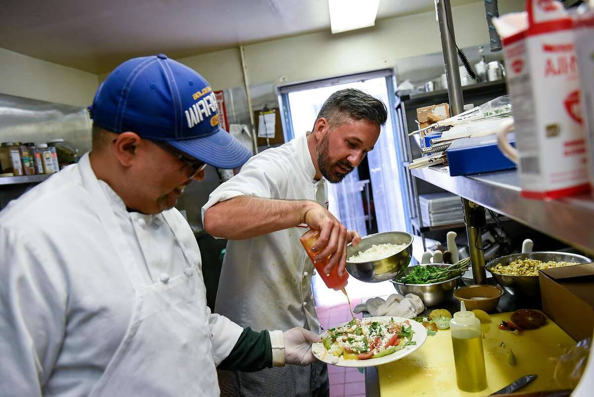"""Chef Jose """"Sonny"""" Lecue, left, watches as head chef Anthony Rizzi tops a plate of tomatoes with chili oil, at the Salvation Army's Harbor Light Treatment Center in San Francisco, CA, on Friday June 30, 2017."""