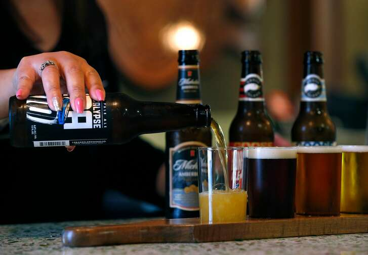 Jennivive Soriano pours a beer flight in the Budweiser tasting room at the Anheuser-Busch brewery in Fairfield, Calif. on Friday, June 30, 2017.