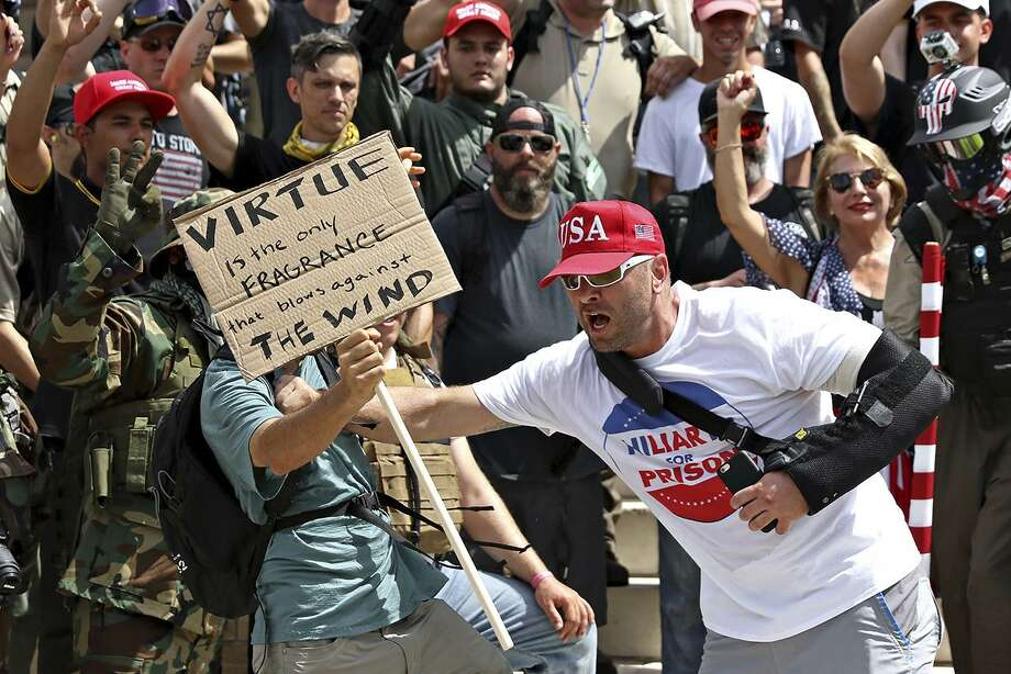 Kevin Kamath, left, and Kyle Chapman, right, get into an altercation at the Texas State Capitol during a march against President Trump, calling for his impeachment July 2 in Austin. Photo: Joshua Guerra /Associated Press / Joshua Guerra
