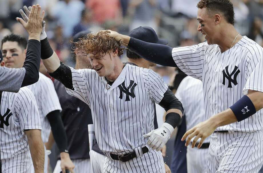 Clint Frazier (center) hit a walk-off home run on July 8 and joins Aaron Judge (right) as rookie Yankees making an impact. Photo: Julio Cortez, Associated Press