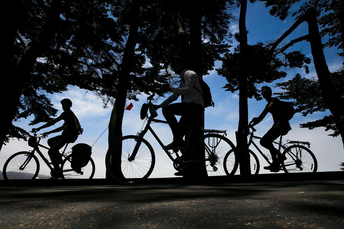 Bikers bike ride in and out of the shadows near Black Point in San Francisco, Calif. Friday, July 14, 2017.