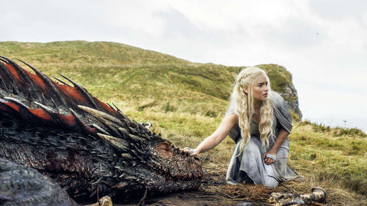 """FILE - In this file image released by HBO, Emilia Clarke appears in a scene from """"Game of Thrones,"""" as the menacing, white-haired Daenerys Targaryen, aka Khaleesi, aka """"Mother of Dragons."""" Even in a world with magic, dragons and deadly supernatural White Walkers, HBO's popular show has plenty of economic lessons to teach. (HBO via AP, File)"""