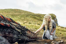 """FILE - In this file image released by HBO, Emilia Clarke appears in a scene from """"Game of Thrones,"""" as the menacing, white-haired Daenerys Targaryen, aka Khaleesi, aka """"Mother of Dragons."""" Even in a world with magic, dragons and deadly supernatural White Walkers, HBOÂ?'s popular show has plenty of economic lessons to teach. (HBO via AP, File)"""