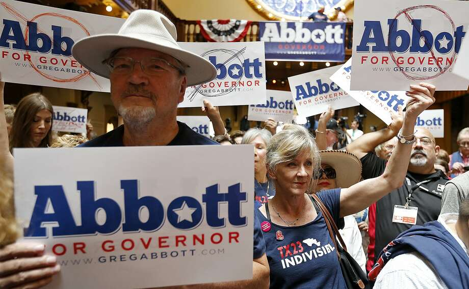 Texas Gov. Greg Abbott supporter Donald Norris (left), protester Janet Oglethorpe (center) and others hold signs during an event where Gov. Abbott (not pictured) announced his bid for re-election Friday July 14, 2017 at Sunset Station. Photo: Edward A. Ornelas, San Antonio Express-News