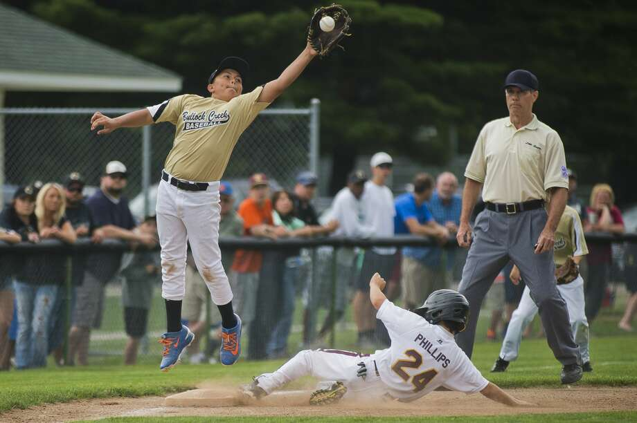 Bullock Creek's Layke Hornung catches the ball as Union Township's Griffin Phillips slides into third base during their district 1 championship game on Friday, July 14, 2017 in Midland. Photo: (Katy Kildee/kkildee@mdn.net)