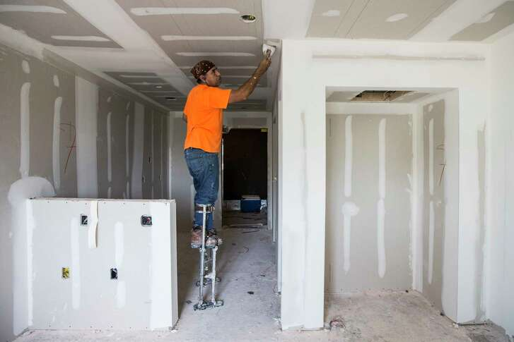 Reuben Reynoso works in one of the resident rooms at New Hope Housing on Harrisburg on Friday, July 14, 2017, in Houston. The complex is being built through bond money slated for housing.