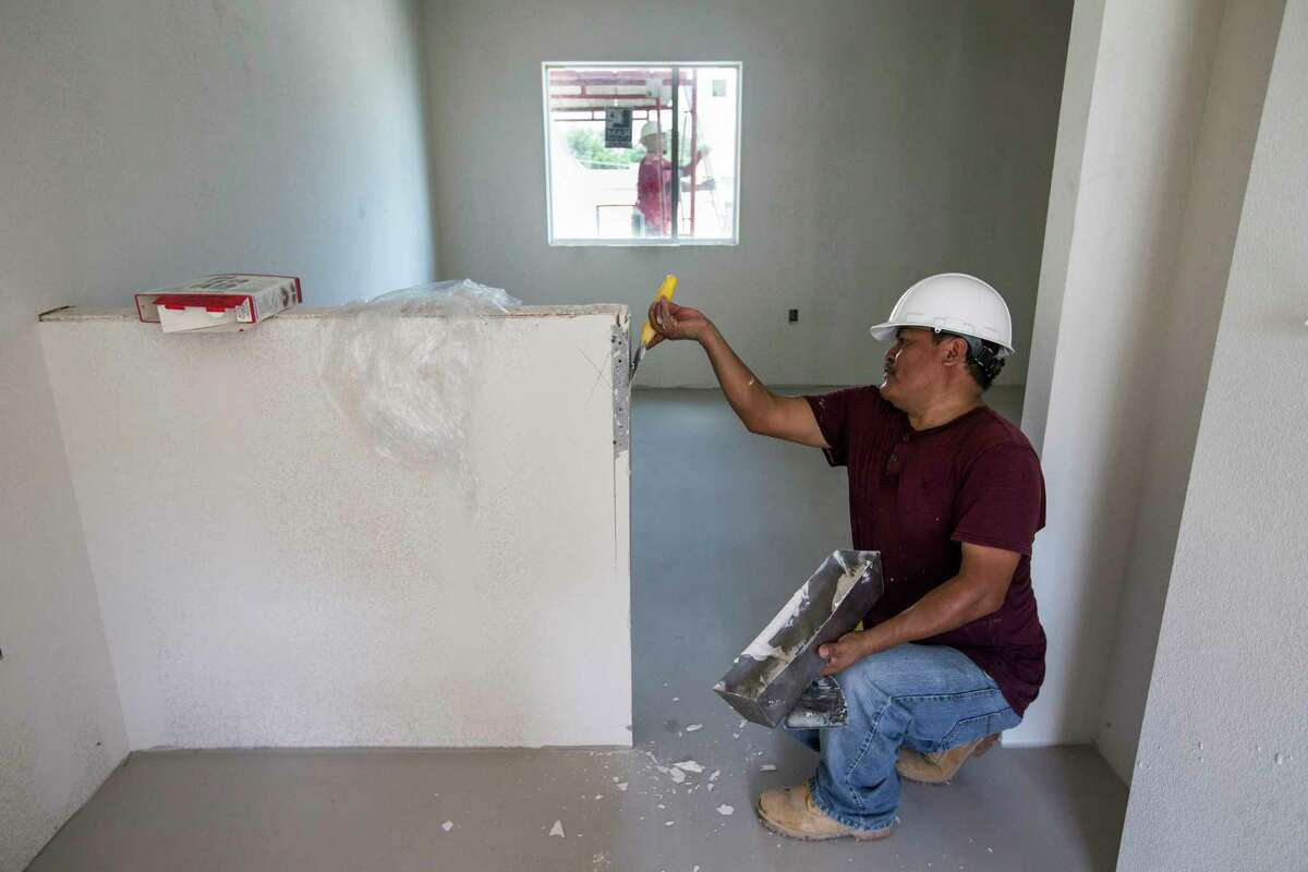 Manuel Cespedes works in one of the resident rooms at New Hope Housing on Harrisburg on Friday, July 14, 2017, in Houston. The complex is being built through bond money slated for housing.