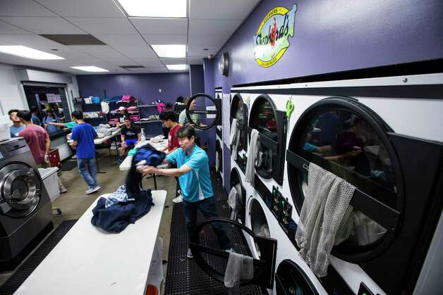 Volunteer Jay Nahm washes clothes for clients of The Beacon homeless services center in the improved laundry facility on Friday, July 14, 2017, in Houston. Improvements were made through bond money slated for housing. Photo: Brett Coomer, Houston Chronicle / © 2017 Houston Chronicle