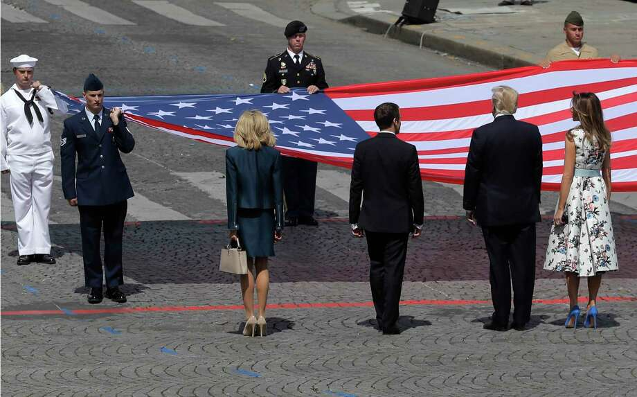 French President Emmanuel Macron, fourth from left, and his wife, Brigitte, to his left, stand with President Donald Trump and first lady Melania Trump as an  American flag is presented during a Bastille Day parade in Paris. Photo: Markus Schreiber, STF / Etienne Laurent