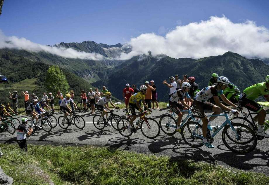 Fabio Aru (yellow jersey, center) is in the middle of the peleton as it heads up the mountains Friday between Saint-Girons and Foix. Photo: JEFF PACHOUD / AFP/Getty Images / AFP or licensors